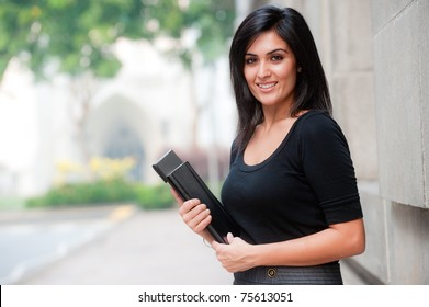A young attractive Asian businesswoman standing outside