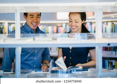 A young and attractive Asian Chinese couple browse books in a library or book store during a date. They are middle-aged, confident and well-dressed.