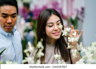 A young and attractive Asian couple stop to smell the flowers in a park during the day. They are both good looking and are smiling as they enjoy a sunny day outside sightseeing together.
