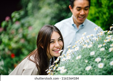A young and attractive Asian couple stop to lean in and smell flowers in a lush, green garden during the day. They are a young and beautiful couple and are comfortably dressed for their vacation.