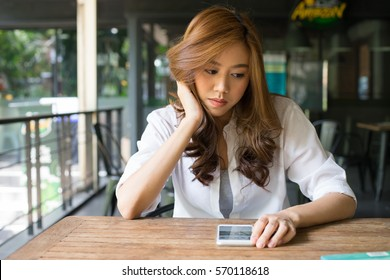 Young attractive asian female chatting on mobile phone