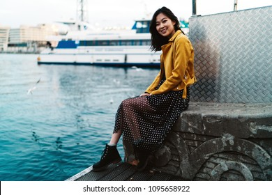 Young attractive asian female with long dark hair wearing maxi chiffon dress, yellow leather jacket and boots is smiling at the camera while sitting at the city berth area on a sunset.