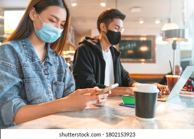 young attractive asian female and male wearing face mask virus protecting social distancing seat working with laptop in coffee shop cafe