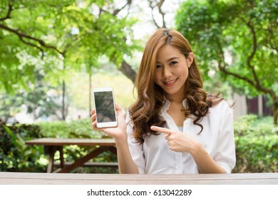 Young attractive asian female pointing at a mobilephone
