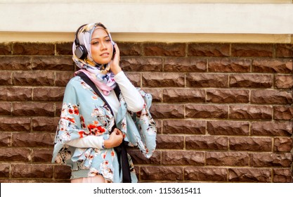 Young attractive Asian girl with hijab enjoying music from her wireless headphone