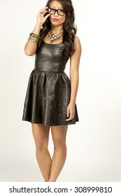 A young attractive Asian girl wearing a leather dress and holding glasses on a white background.