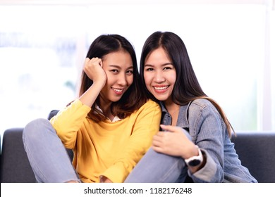 Young attractive asian girlfriends sitting together at couch sofa at home smiling and looking at camera in lover feeling happy lgbt lesbian. Beautiful homosexual couple women or bestfriends concept.