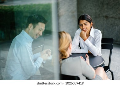 A young and attractive Asian Indian woman is interviewing for a job. Her interviewers are diverse -- one is a Chinese man, the other a Caucasian woman. They are talking in an office and smiling.