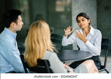 A young and attractive Asian Indian woman is interviewing for a job. Her interviewers are diverse -- one is a Chinese man, the other a Caucasian woman. The Indian woman is gesturing as she talks.
