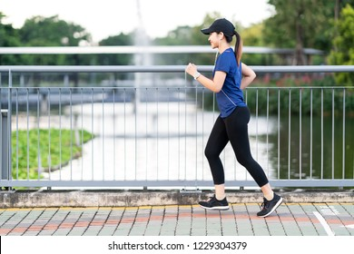 Young attractive asian runner woman running at sidewalk way in public nature city park with lake water view wearing blue or black sporty sportswear with copy space in morning walk workout concept.