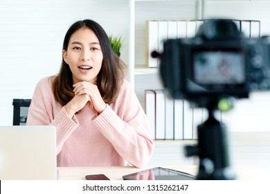 Young attractive asian woman blogger or vlogger looking at camera and talking on video shooting with technology. Social media influencer people or content maker concept in relax casual style at home.