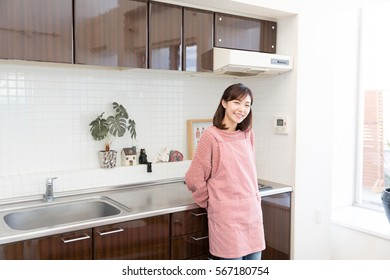 young attractive asian woman cooks in a kitchen