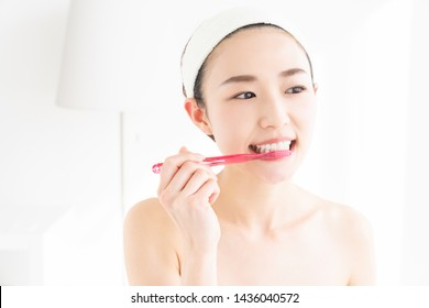 young attractive asian woman with healthy teeth holding a tooth brush,oral care