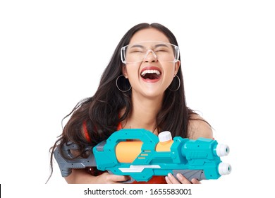 Young attractive Asian woman with healthy skin wearing orange t-shirt ,glasses holding turquoise water gun with smiley face isolated on white. Songkran festival.
