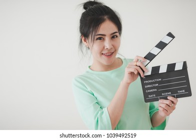 Young attractive Asian woman holding clapperboard with positive feeling. Film production and movie making concept