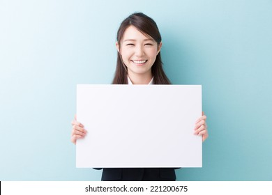 young attractive asian woman holding blank white board