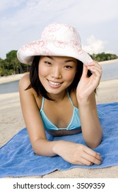 A young attractive asian woman lying on the beach