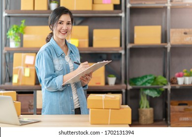 Young attractive asian woman owner startup business look at camera work happy with box at home prepare parcel delivery in sme supply chain, procurement, omnichannel or coronavirus quarantine concept.