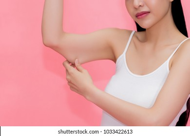 Young attractive Asian woman pinching excess fat and cellulite in her upper arms as she lacks exercise and healthy lifestyle