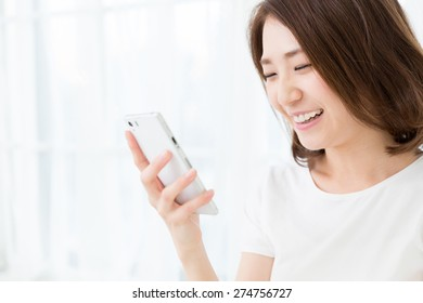 young attractive asian woman  to see a smart phone
