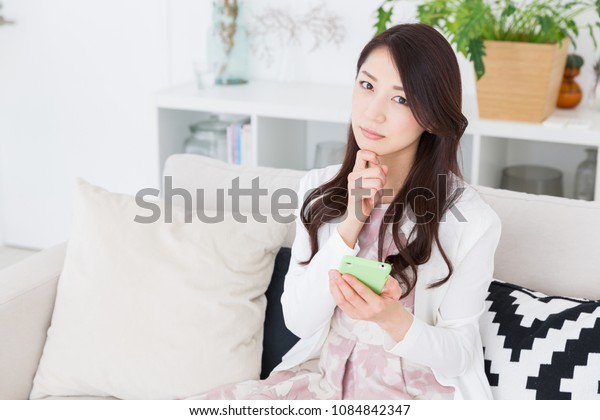 young attractive asian woman to see a smart phone,think,