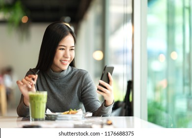 Young attractive asian woman smiling, texting and messaging in mobile phone's app for online payment or money transfer and looking at notification on smartphone feeling positive in cafe coffee shop.