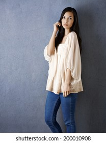 Young attractive Asian woman standing by grey wall, posing, looking at camera.