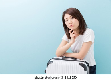 young attractive asian woman and suitcase to think about
