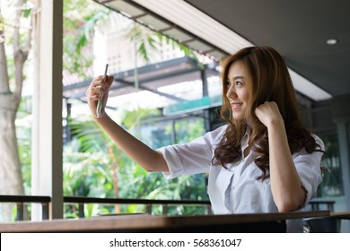 Young attractive asian woman taking selfie at a cafe
