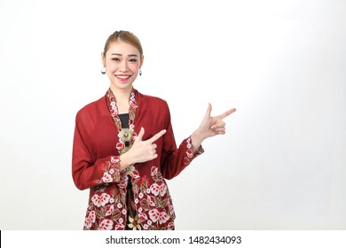 Young attractive Asian woman traditional red maroon nyonya kebaya sharong on white background happy smile pointing right