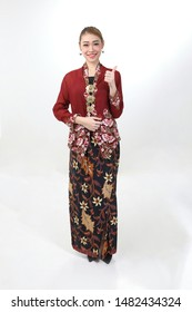 Young attractive Asian woman traditional red maroon nyonya kebaya sharong on white background happy smile confident