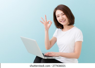 young attractive asian woman using laptop
