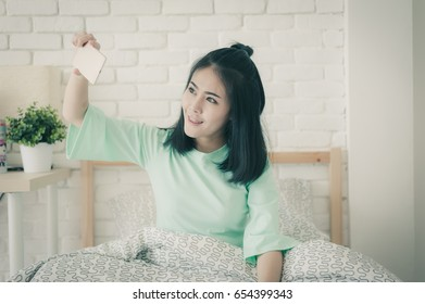 Young attractive Asian woman wear green casual cloths taking selfie photo while sitting on bed. Lazy girl activity on sunday morning with vintage filter effect