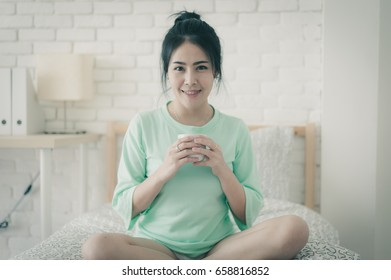 Young attractive Asian woman wear green casual cloth holding coffee cup while sitting on bed. Lazy girl activity with coffee on sunday morning with vintage filter effect