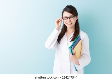 Young attractive asian woman in a white coat