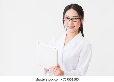 Young attractive asian woman in a white coat,tablet PC