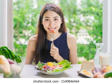 young attractive asian woman who eats with vegetable salad on the table indoors. Green healthy food concept.