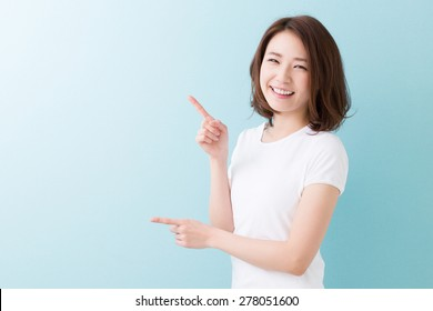 young attractive asian woman who points to the finger