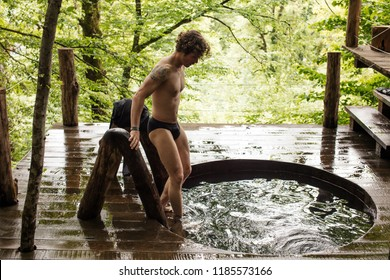 young attractive awesome man is testing new wooden bathtub which is situated in the forest.