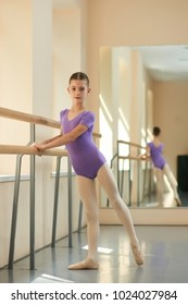 Young attractive ballerina near barre. Beautiful girl standing near railing in ballet class. Workout at ballet studio.