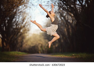 Young attractive ballerina training at the spring garden. Fine art ballet concept. Surreal dancing. Teenager girl jump over the old park lane. Concept of new life beginning. Active and healthy kid