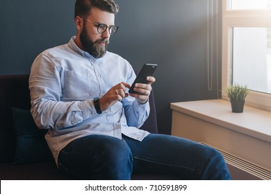 Young attractive bearded businessman in shirt and glasses sits on sofa in room and uses smartphone. Hipster man working, learning, blogging, chatting online. Social media, network. Online education.
