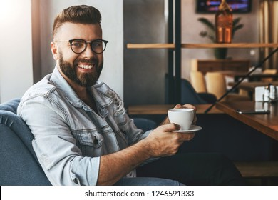 Young attractive bearded businessman in trendy glasses sits in cafe, drinks coffee during lunch time, rests, enjoys drink. Hipster guy waiting for friends in coffee shop. Lifestyle, leisure, pastime.