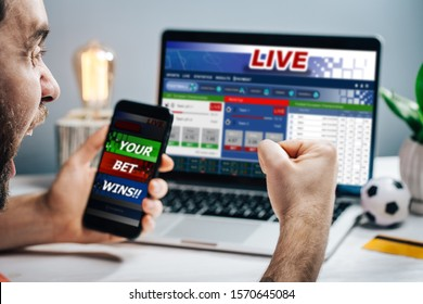 Young attractive bearded man showing sincere excitement about his favorite team victory. Guy being happy winning a bet in online sport gambling application on his mobile phone.