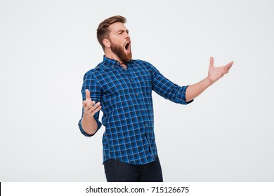 Young attractive bearded man singing loud while standing isolated over white background