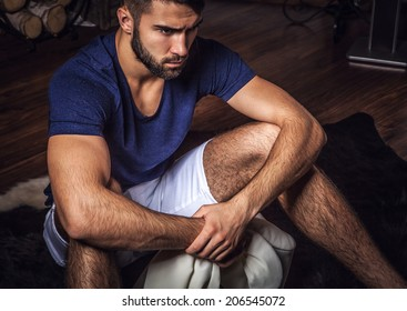 Young attractive bearded men pose in modern room. Close-up photo.