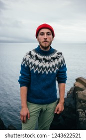 Young attractive bearded millennial man in red fisherman or sailor beanie hat and traditional icelandic ornament blue sweater stands on seaside on cloudy day, serious and tough personality