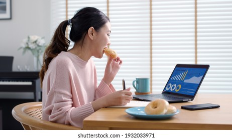 Young attractive beautiful asian female hungry eat doughnut take away snack food with full mouth look at computer notebook at home in busy work from home multitask unhealthy meal lifestyle concept.