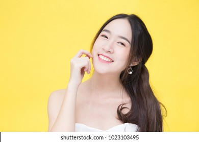 Young attractive and beautiful Asian woman with pure white and perfect smooth skin with fresh and beauty face posting and smiling to camera isolated on yellow background