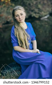 Young attractive beautiful blonde girl in blue dress sitting on old tire from wheel near water. She looks at the camera. Photoshoot outdoor